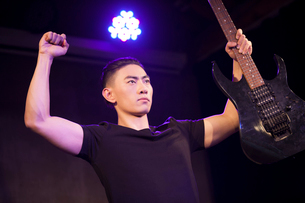 Young man with guitar on stageの写真素材 [FYI02225558]
