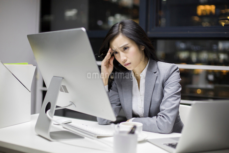 Businesswoman working late in officeの写真素材 [FYI02225595]