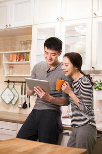 Young couple using digital tablet in kitchenの写真素材 [FYI02225619]