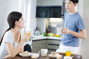 Happy young couple having breakfast at homeの写真素材 [FYI02225651]