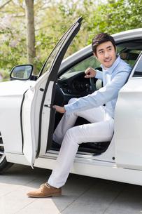 Young man opening car doorの写真素材 [FYI02225657]