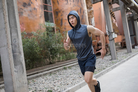 Young Chinese man jogging outdoorsの写真素材 [FYI02225669]