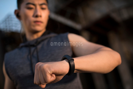 Young Chinese man checking smart watch after runningの写真素材 [FYI02225681]