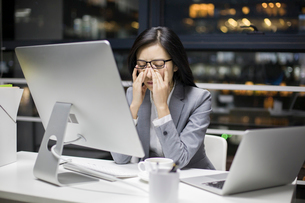 Businesswoman working late in officeの写真素材 [FYI02225689]