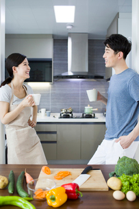 Happy young couple drinking coffee in kitchenの写真素材 [FYI02225766]