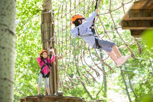 Little girls playing in tree top adventure parkの写真素材 [FYI02225809]