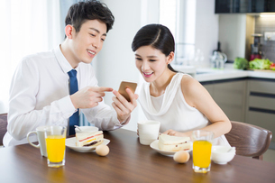 Happy young couple having breakfast at homeの写真素材 [FYI02225831]