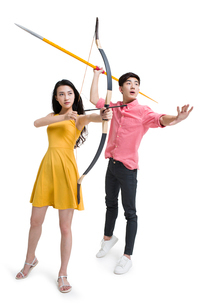 Young couple holding bow and arrowの写真素材 [FYI02225842]