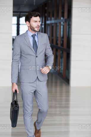 Confident businessman walking with briefcaseの写真素材 [FYI02225862]