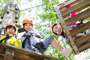 Happy children playing in tree top adventure parkの写真素材 [FYI02225875]
