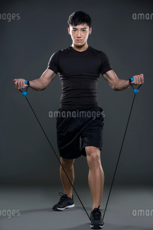 Young man exercising with resistance bandの写真素材 [FYI02225898]