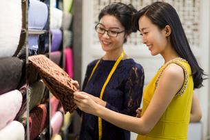 Chinese fashion designer helping customer choosing fabric swatchの写真素材 [FYI02225903]