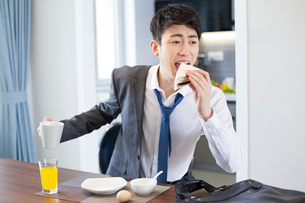 Young businessman having breakfast in a hurryの写真素材 [FYI02225915]