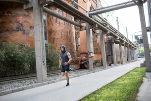 Young Chinese man jogging outdoorsの写真素材 [FYI02225936]