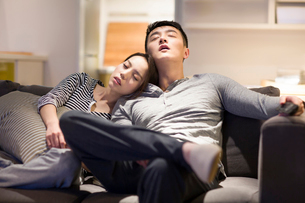 Tired couple sleeping on living room sofaの写真素材 [FYI02225959]