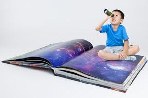 Happy little Chinese boy looking through telescopeの写真素材 [FYI02225965]