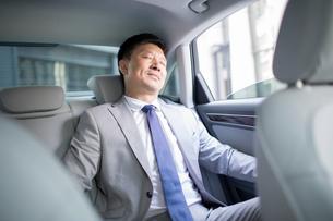 Confident businessman sitting in car back seatの写真素材 [FYI02225975]