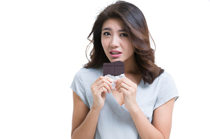 Young woman eating chocolateの写真素材 [FYI02225998]
