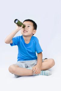 Happy little Chinese boy looking through telescopeの写真素材 [FYI02226009]