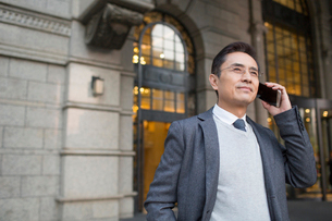 Confident Chinese businessman talking on the phoneの写真素材 [FYI02226015]