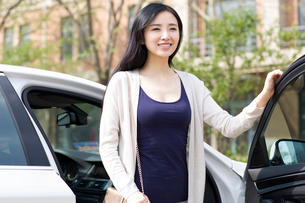 Young woman getting out of a carの写真素材 [FYI02226188]