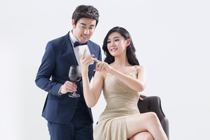 Elegant young Chinese couple using smart phoneの写真素材 [FYI02226200]