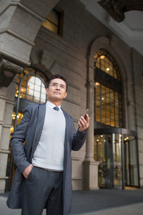 Confident Chinese businessman holding a smart phoneの写真素材 [FYI02226201]