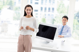Young Chinese businesswoman drinking coffee in officeの写真素材 [FYI02226206]