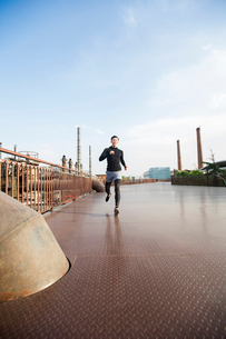 Young Chinese man jogging outdoorsの写真素材 [FYI02226232]