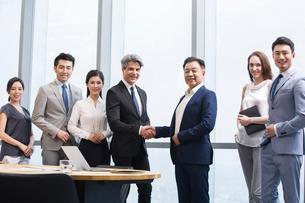 Businessmen shaking hands in meeting roomの写真素材 [FYI02226235]