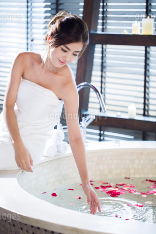 Beautiful young woman sitting by the bathtubの写真素材 [FYI02226265]