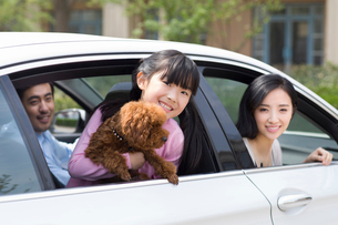 Happy young family with their pet dog sitting in carの写真素材 [FYI02226278]