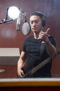 Young man singing with guitar in recording studioの写真素材 [FYI02226291]