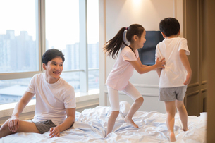 Cheerful young Chinese family having fun on a bedの写真素材 [FYI02226331]