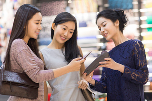 Chinese friends paying with smart phone in clothing storeの写真素材 [FYI02226337]