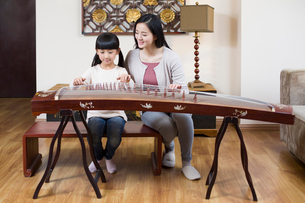 Mother teaching traditional musical instrument zitherの写真素材 [FYI02226366]