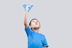 Happy little Chinese boy throwing a paper airplaneの写真素材 [FYI02226373]