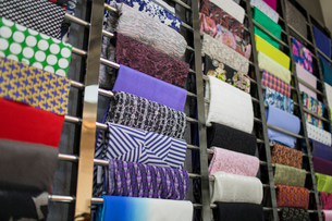 Different fabric swatches hanging on a designer's material rackの写真素材 [FYI02226421]