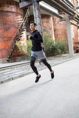 Young Chinese man jogging outdoorsの写真素材 [FYI02226422]