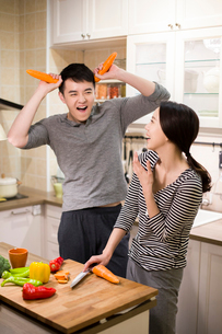 Young couple cooking in kitchenの写真素材 [FYI02226426]