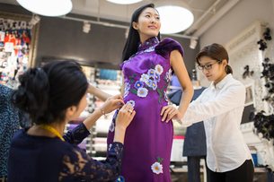 Chinese fashion designers adjusting customer's dressの写真素材 [FYI02226446]