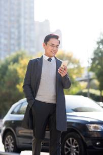 Confident Chinese businessman using smart phoneの写真素材 [FYI02226490]