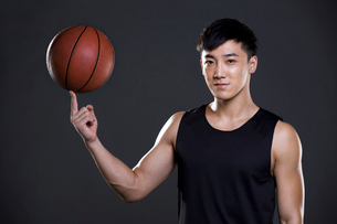 Young man spinning basketball on fingerの写真素材 [FYI02226547]