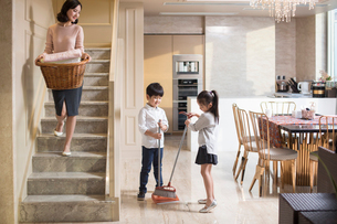 Happy Chinese family doing laundry and sweeping at homeの写真素材 [FYI02226560]