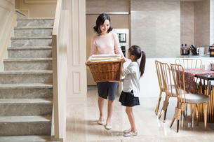 Young Chinese mother and daughter doing laundry at homeの写真素材 [FYI02226569]