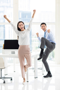 Confident Chinese business people cheering in officeの写真素材 [FYI02226579]