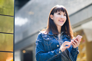 Young woman holding a smart phoneの写真素材 [FYI02226589]