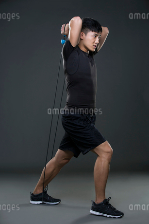 Young man exercising with resistance bandの写真素材 [FYI02226591]