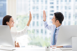 Confident Chinese business people high fiving in officeの写真素材 [FYI02226612]
