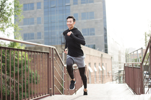 Young Chinese man jogging outdoorsの写真素材 [FYI02226628]